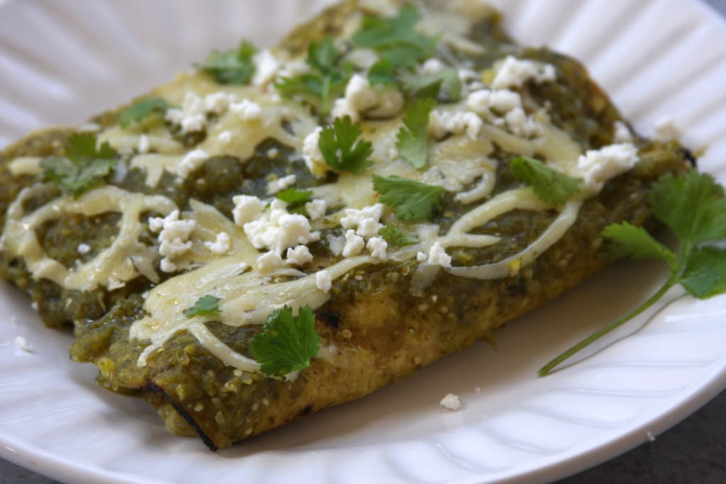 Lightened Up Salsa Verde Chicken Enchiladas recipe is bursting with the light & refreshing flavors of tomatillo and cilantro. Pepper Jack & Queso Fresco add a wonderful creaminess and yet this recipe is lighter than your traditional enchilada.