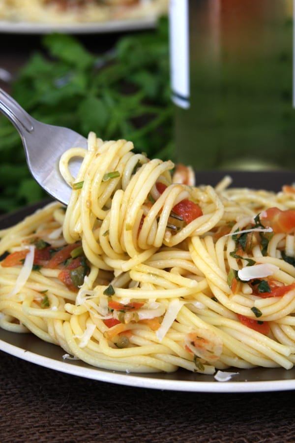 Tomato Caper Pasta is a light & savory dish. Capers, thinly sliced garlic, fresh tomatoes and Italian parsley surround tantalizing al dente pasta. Have this with a glass of chilled white wine and you will feel carried away to a dinner in Italy.
