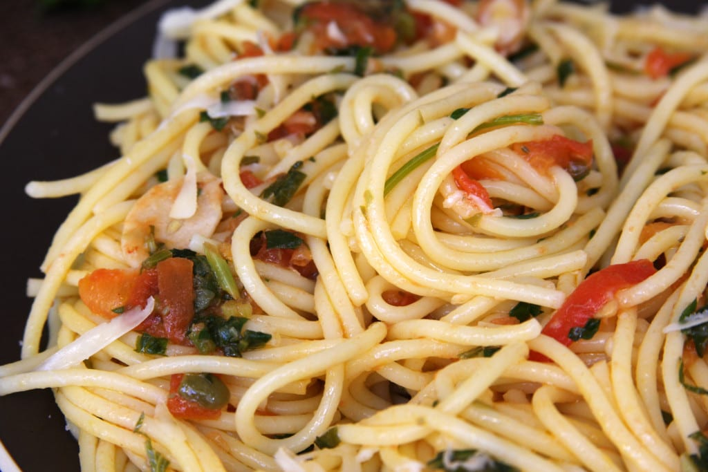Tomato Caper Pasta recipe is a perfect light & savory dish for summer with a glass of chilled white wine. We loved the simple flavors of capers, garlic, fresh tomatoes and Italian parsley all nestled in a bed of al dente pasta. This recipe feels so gourmet but is very easy to make.