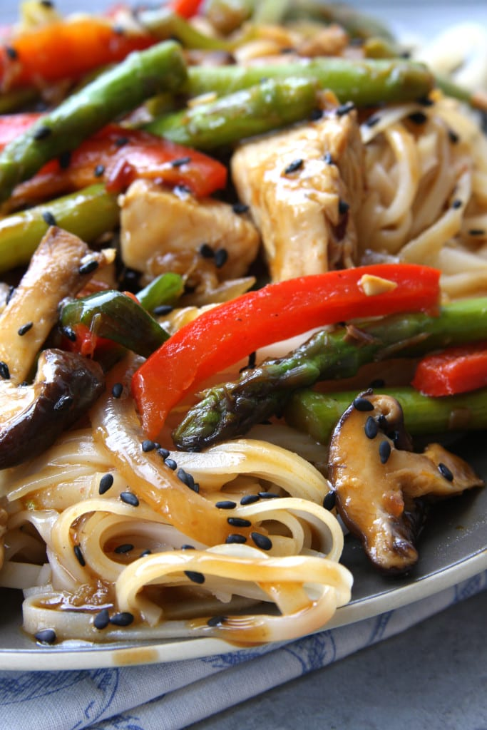 Lemongrass Chicken Noodle Stir Fry recipe Is healthy decadence on a plate. Packed with a ton of veggies and comforting rice noodles. It will make you want to curl of on the couch and indulge.