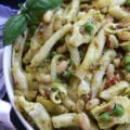 Hearty Tuscan Pasta recipe has cannellini beans, pancetta, sun-dried tomatoes, artichoke hearts, peas and pesto. Comes together within a half hour and is the perfect meal to impress company. This is my new favorite go to pasta.