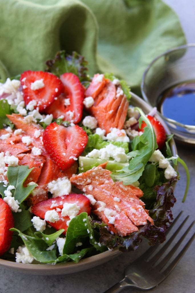Simple Strawberry Salmon Salad recipe is an easy and healthy meal. Simple olive oil balsamic vinaigrette surrounds juicy strawberries, wild Atlantic salmon and creamy feta. We adore this salad on hot summer nights.