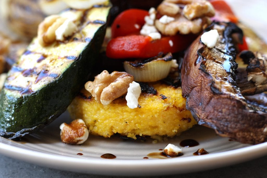 Rustic Italian Grilled Polenta & Vegetables recipe is a healthy & savory dish great for sharing. Polenta has flavors of rosemary and parmesan and is surrounded by grilled veggies and a balsamic reduction. Portable, tasty and vegetarian.