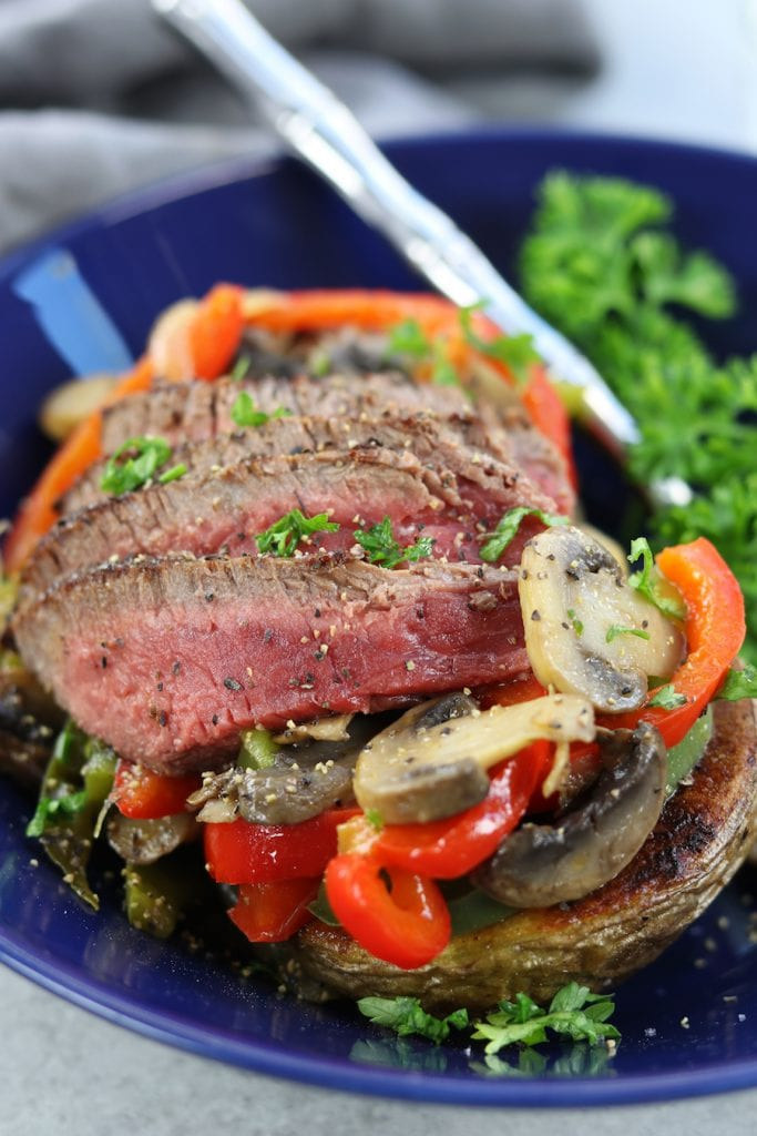 Veggie Cheesesteak Potatoes recipe has tender steak, red wine sautéed veggies, creamy homemade cheese sauce over a crispy potato.