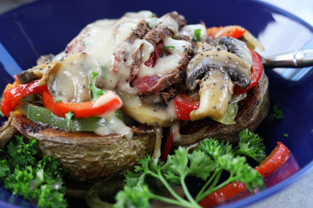 Veggie Cheesesteak Potatoes recipe has tender steak, red wine sautéed veggies, creamy homemade cheese sauce over a crispy potato.