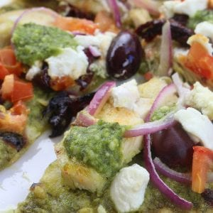 Easy and delicious, Chicken Pesto Naan Pizza comes together in minutes with kalamata olives, goat cheese and red onions. Perfect for busy weeknights without composing flavor.