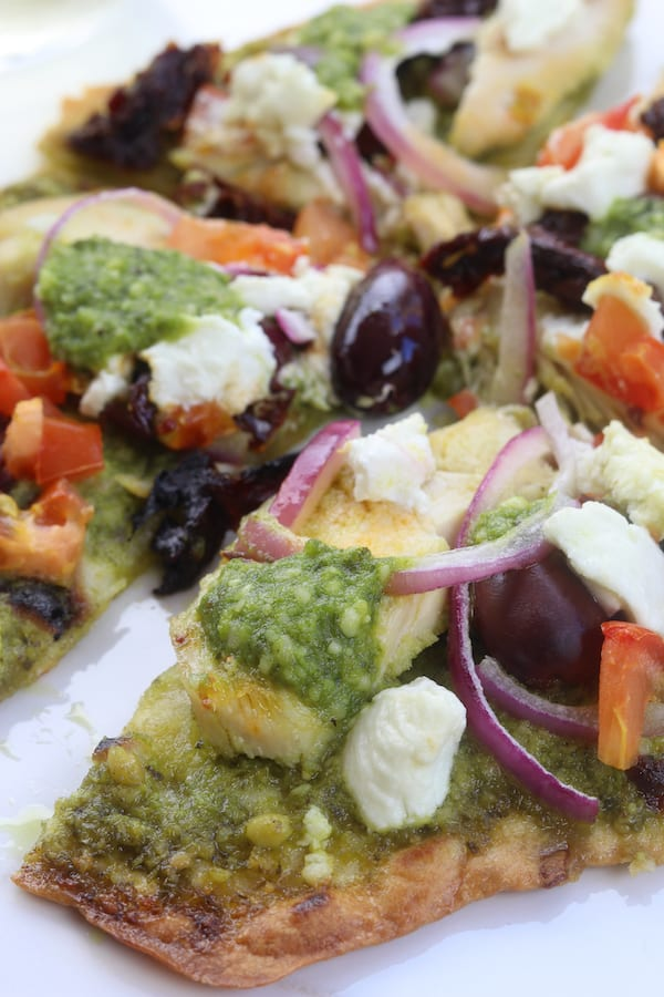 Easy and delicious, Chicken Pesto Naan Pizza comes together in minutes with kalamata olives, goat cheese and sun-dried tomatoes. Perfect for busy weeknights without composing flavor.