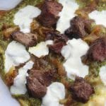 Caramelized Onion Steak Naan Pesto Pizza has the perfect marriage of sweet buttery caramelized onions, herby pesto and satisfying steak. Ingredients can be made ahead of time for a delicious dinner that comes together in a little over 10 minutes.