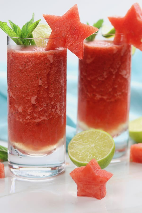Frozen Watermelon Mojitos is the drink of summer! An adult-beverage speckled with mint, a hint of lime, watermelon simple syrup and incredibly refreshing icy watermelon. It is dangerously delicious!