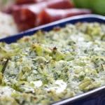 Close up of Baked Lemon Artichoke Dip with a drizzle of olive oil.