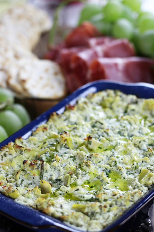 Best Artichoke Dip on a table with grapes, prosciutto and crackers.