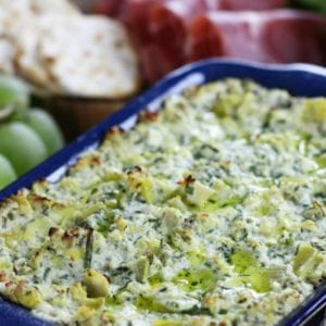 Lemon Artichoke Dip sitting among other appetizers