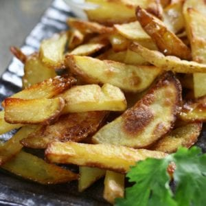 Homemade French Fries with ranch dressing on a dark plate.