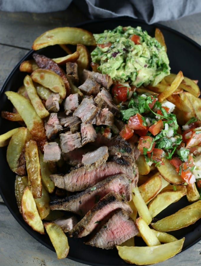 Overhead picture of Carne Asada Fries on a black plate.