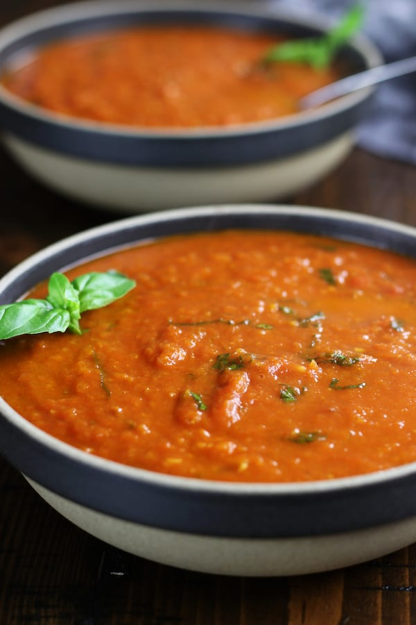 Two servings of Easy Tomato Basil Soup with fresh basil.