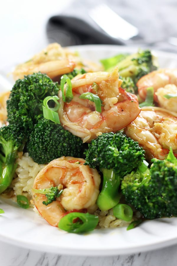 A plate of Garlic Shrimp Stir Fry on a bed of rice.