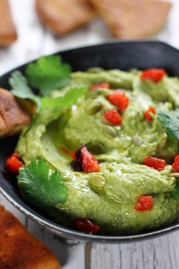 Smooth Avocado Hummus with roasted red bell peppers and cilantro.