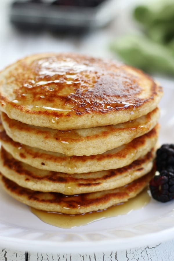 Easy Oat Flour Pancakes on a white plate with blackberries.