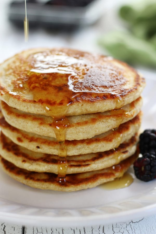 Syrup being poured on a stack of Gluten Free Oatmeal Pancakes.