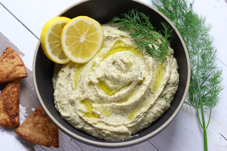 A bowl of Lemon Garlic Hummus sitting on a white table.
