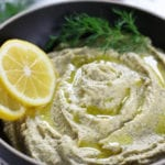 Lemon Hummus with a sprig of fresh dill and two slices of lemon.