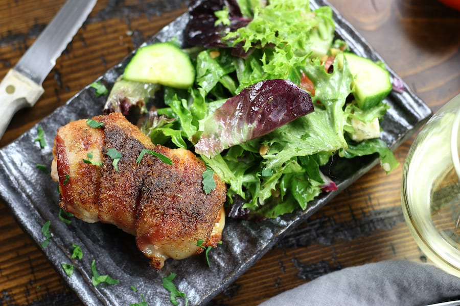 Stuffed Chicken Breast Recipe on a dinner plate with salad.