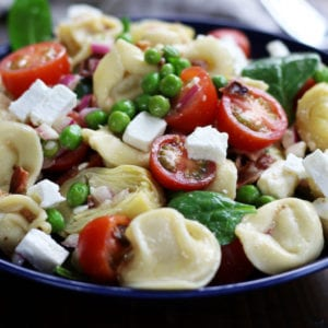 Tortellini Pasta Salad in a bowl with tomatoes, peas, bacon, feta and spinach.