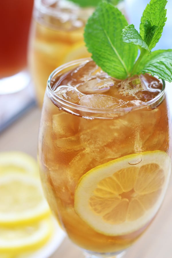 Glass full of Ice Tea with lemon slice and mint leaves.