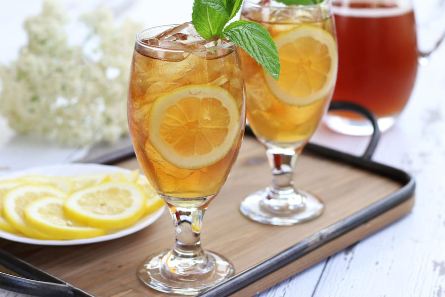 Two glasses of Iced Tea sitting on a tray with lemon slices.