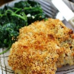 Crispy Baked Pork Chops recipe on a plate with spinach.