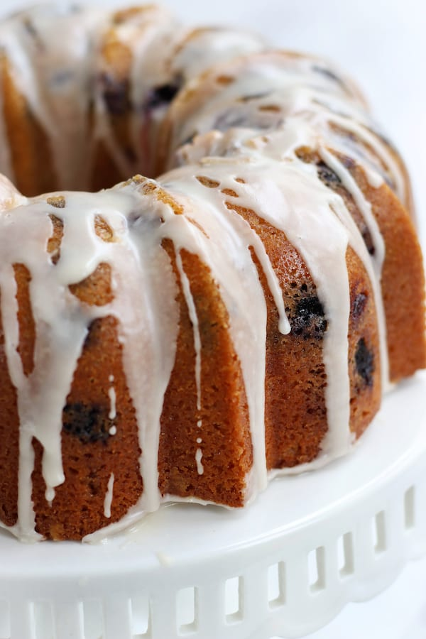 Lemon Blueberry Cake in a bundt shape on a cake stand.