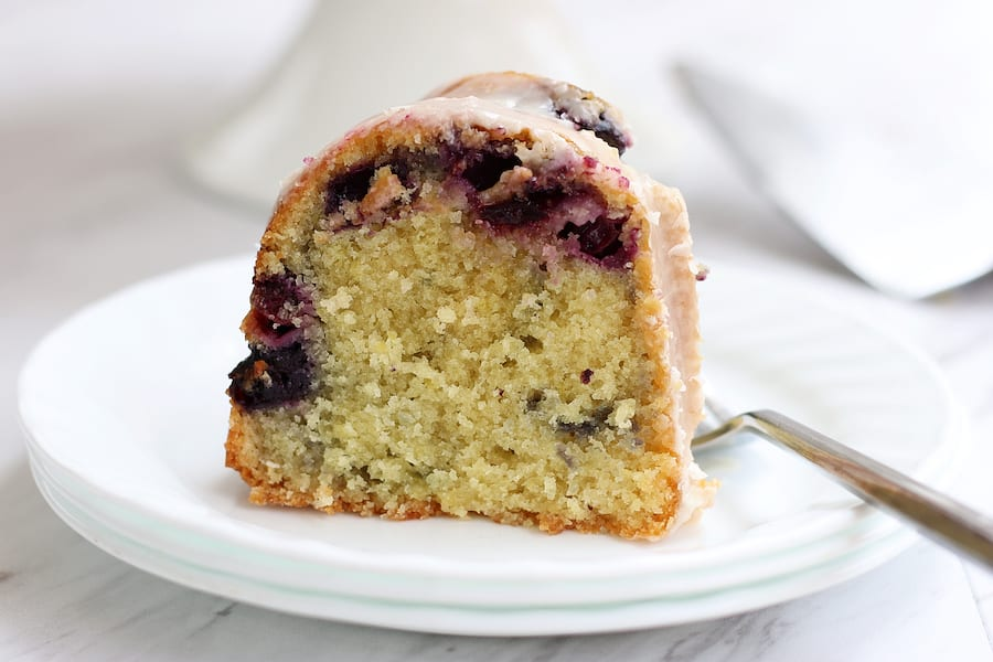 Lemon and Blueberry Cake slice on a white plate with a fork.