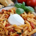Penne Pomodoro with Burrata in a pan, garnished with basil.