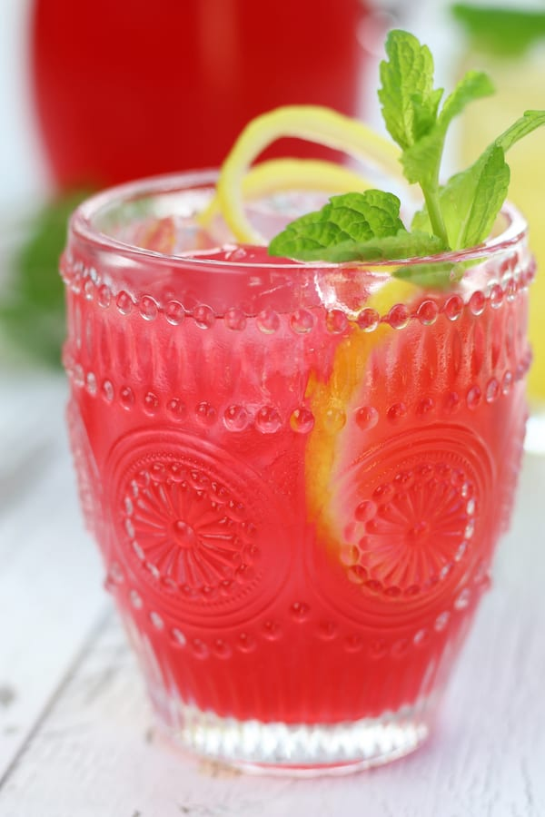 Pink Lemonade in a glass with mint and lemon twist.
