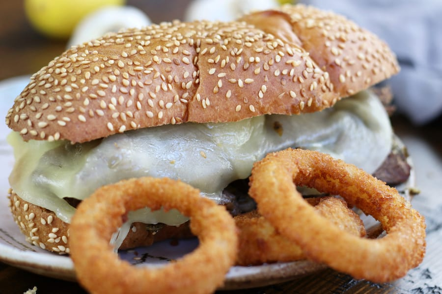 up close photo of Roast Beef Sandwich Recipe on a plate with onion rings.
