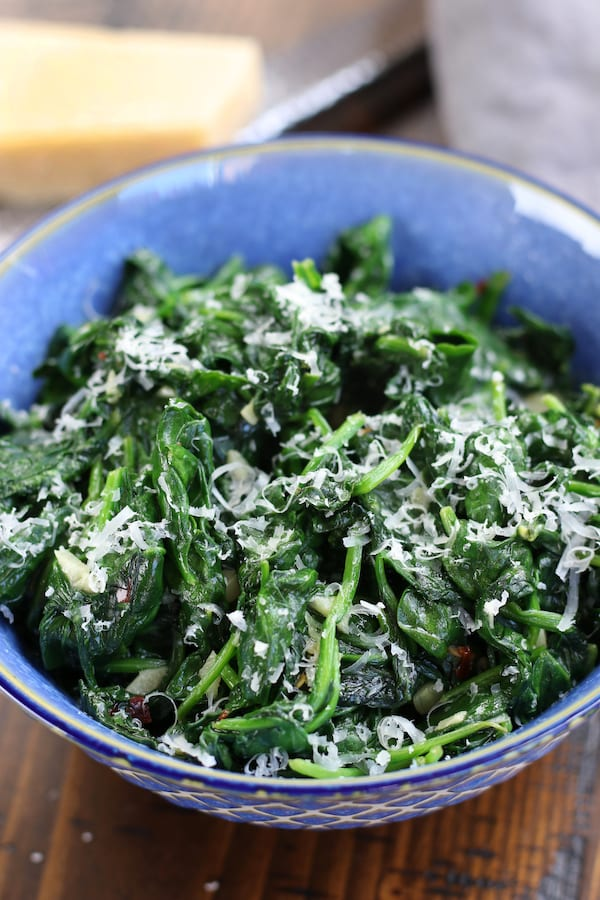 Sautéed Spinach in a blue bowl with parmesan.