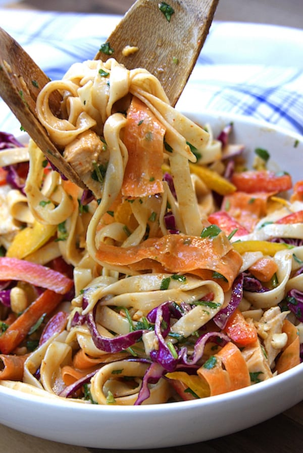 Tongs portioning out Chicken Peanut Udon Noodle Salad.