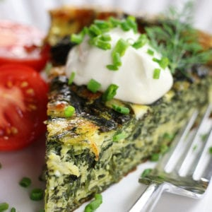 Piece of Crustless Spinach Quiche garnished with chives and sour cream.