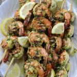Marinated Grilled Shrimp Kabobs on a white plate with lemon wedges.