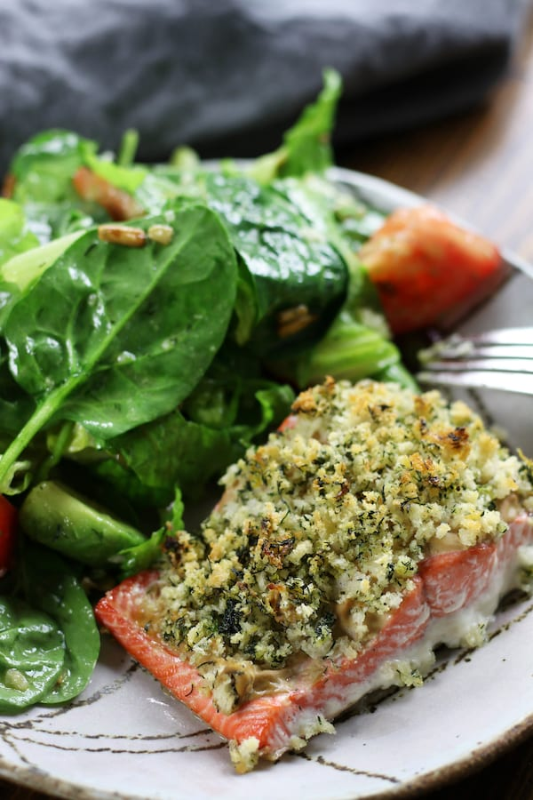Panko Crusted Salmon on a plate with spinach salad.