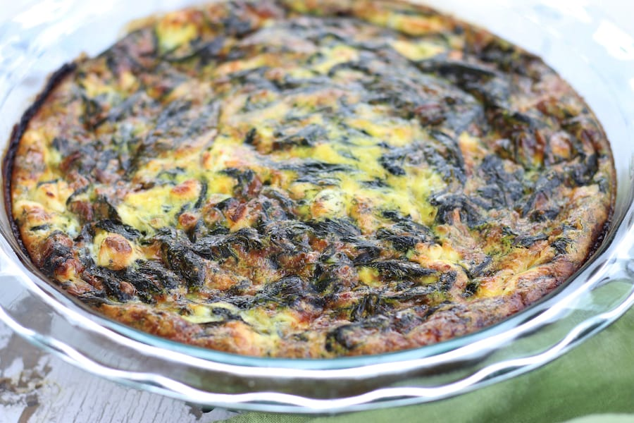 Spinach Quiche in a clear pie plate with a scalloped edge.
