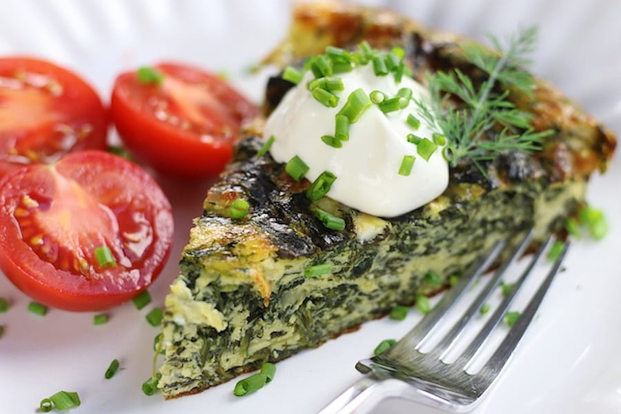 Spinach and Feta Quiche slice with fresh cut tomatoes.