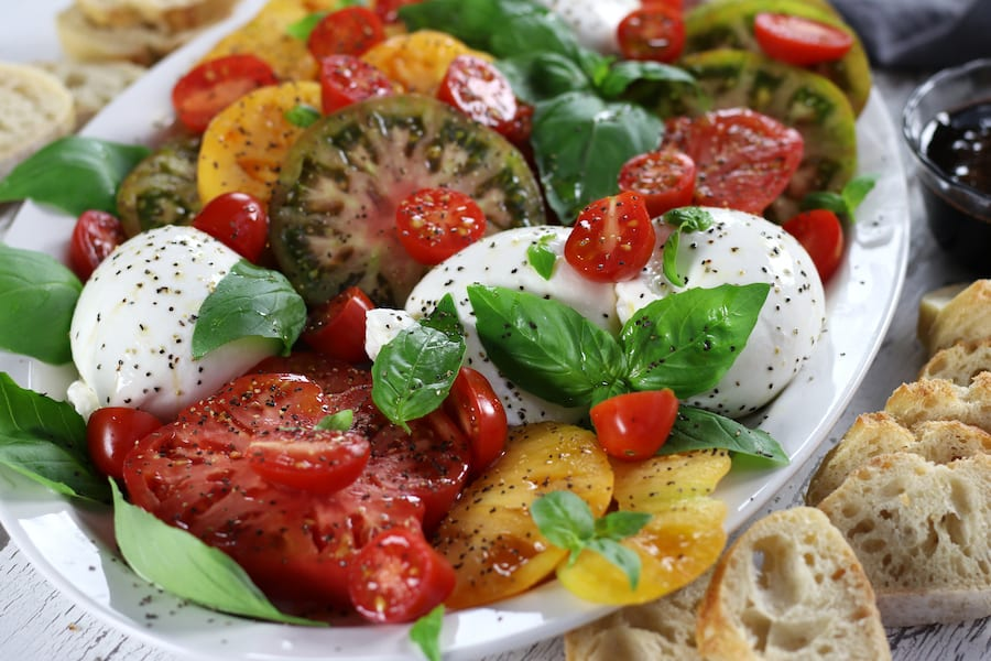 Caprese Salad Recipe served on a platter with fresh cut baguette bread.