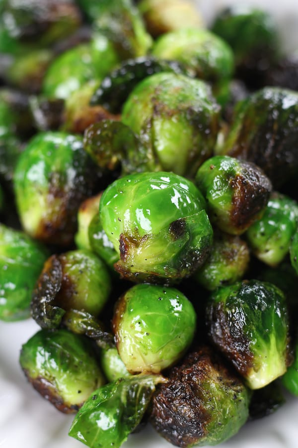 Brussel Sprouts on a white plate from Grilled Brussel Sprouts Recipe.