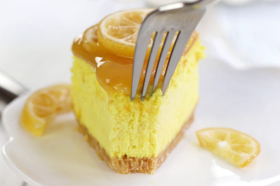 Fork cutting into slice of Lemon Curd Cheesecake.