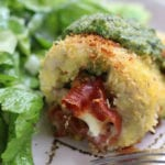 Pesto Chicken Rollatini on a plate with salad.