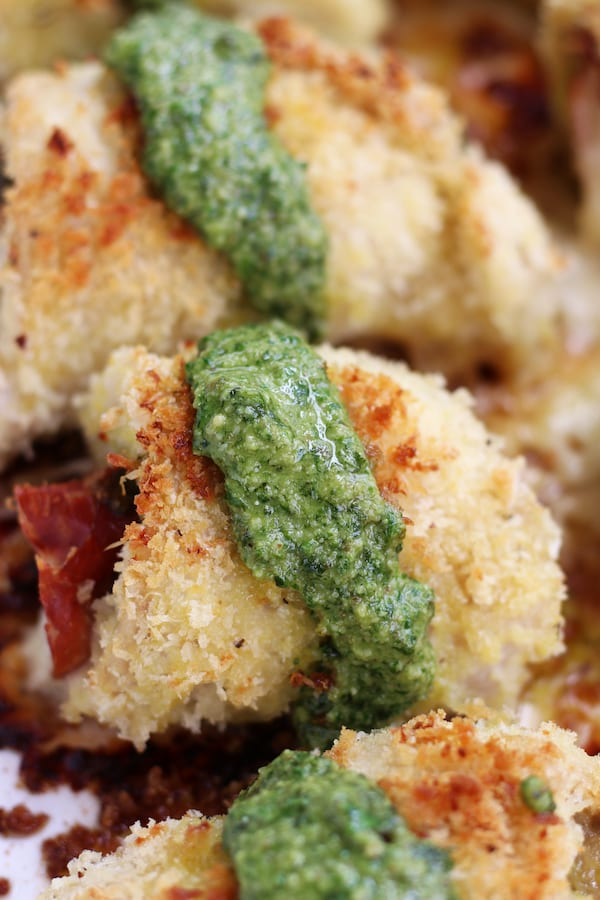 A row of Stuffed Chicken rolls covered in Panko with pesto.
