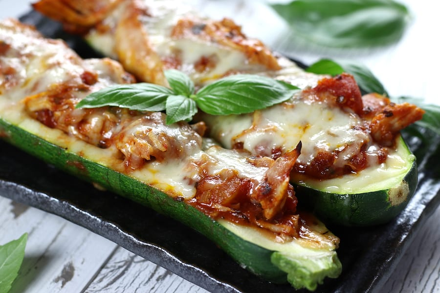 Chicken and Zucchini Boats on a grey plate garnished with basil.