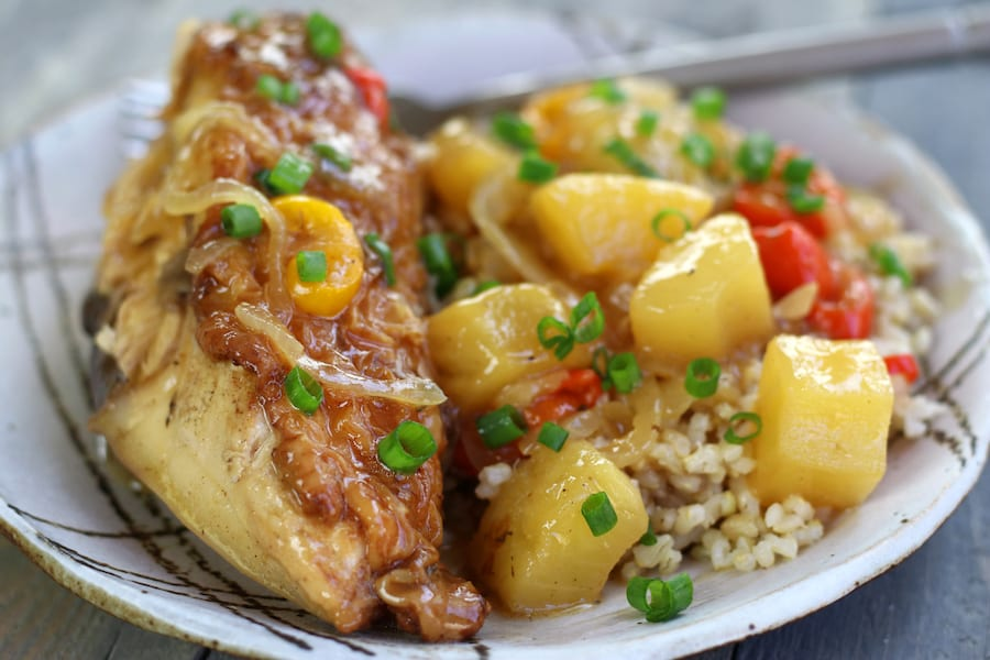 A plateful of Healthy Sweet and Sour Chicken with a chicken breast and brown rice.