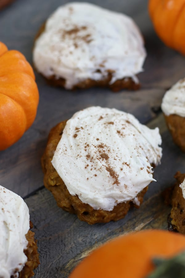 Old Fashioned Pumpkin Cookies sitting on a wooden table with small pumpkins.